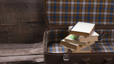 Books in an old leather checkered suitcase. Vintage background.
